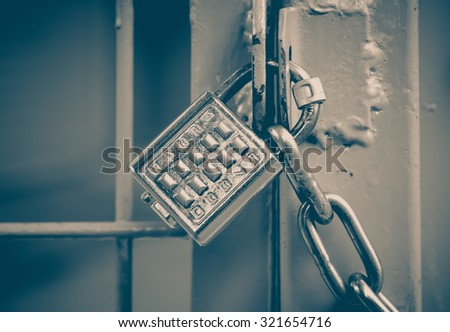 Metal padlock and pin keypad with numbers on metal door - stock photo