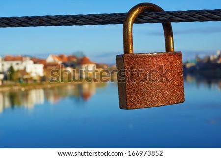 Metal padlocks of love hanging on fence in Maribor - stock photo
