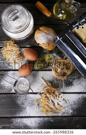 Metal pasta maker machine and ingredients for pasta on wooden background - stock photo