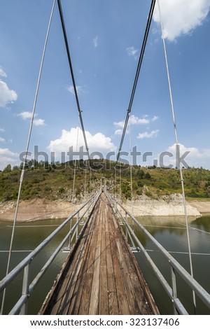 Metal pedestrian suspension bridge over river Uvac in the special nature Reserve Uvac, Serbia. Shallow DOF. - stock photo