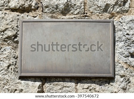 Metal plaque mounted on an old stone wall. - stock photo