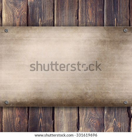 Metal plate on wooden background - stock photo
