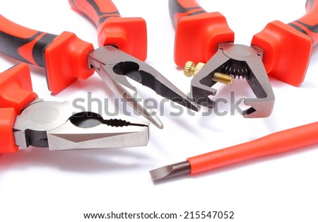 Metal pliers, insulation stripper pliers for insulating electric wires, screwdriver on white background, work tools for engineering - stock photo