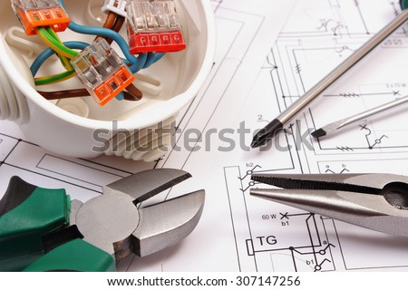 Metal pliers, screwdriver and cable connections in electrical box lying on electrical construction drawing of house, work tool and drawing for engineer jobs, concept of building house - stock photo