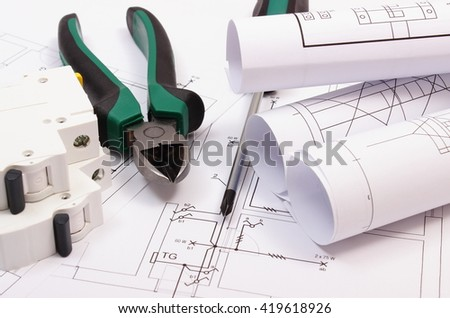 Metal pliers, screwdriver, electric fuse and rolls of diagrams on construction drawing of house, work tool and drawing for projects engineer jobs, concept of building house - stock photo