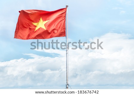 Metal pole with waving banner. Red flag with yellow star, blue sky with clouds in background. Rippled texture. National flag of Vietnam. Popular country for tourism. Famous tourist destination. - stock photo
