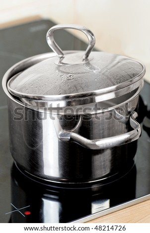Metal pot on the glass stove - stock photo