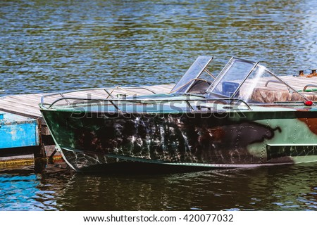 Metal powerboat camouflage painting stand at the pier close-up  - stock photo