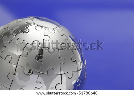 Metal puzzle globe isolated on white background, close-up on blue background - stock photo