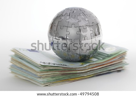 Metal puzzle globe with money on white background - stock photo
