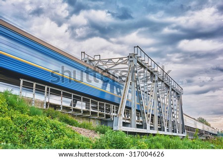 Metal railway bridge and train passes by at great speed - stock photo