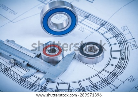 Metal roller bearings and trammel caliper on blueprint construction concept. - stock photo