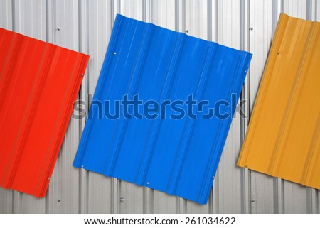 Metal roof painted by red, blue, yellow color for sale - stock photo