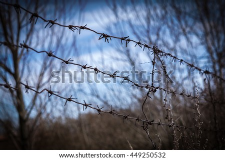 Metal rusty barbed wire border with thorns. Vintage dark toned effect. Freedom concept - stock photo