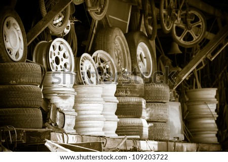Metal second hand shop with used wheels and tyres - stock photo
