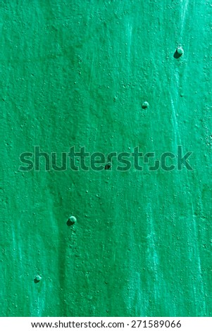 Metal sheet with rivets along the diagonal painted in green and turquoise color in bright sunlight - stock photo