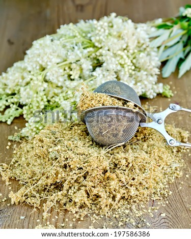 Metal sieve with dried meadowsweet, a bouquet of fresh flowers on a wooden boards background