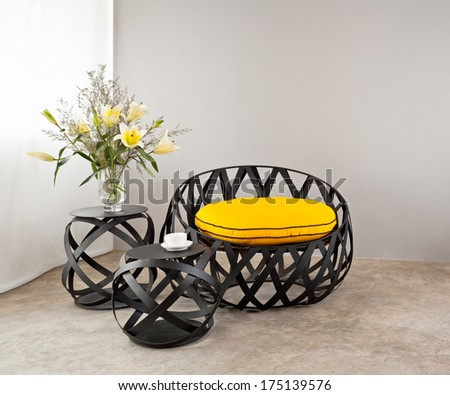 Metal sofa with yellow pillow and lily flowers - stock photo