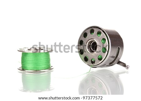 Metal spool of thread and sewing machine shuttle isolated on white - stock photo