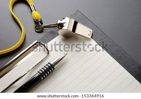 Metal sport whistle with pen and paper sheet - stock photo