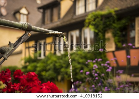 Metal spout of a spring in small town in Alsace region of France - stock photo