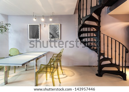 Metal staircase and a plastic chairs and table - stock photo