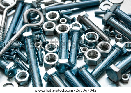Metal style. Fixing elements. Nuts, washers and bolts on scratched metal background. - stock photo