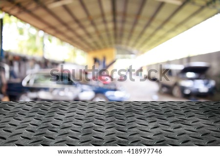 Metal table on garage background.
