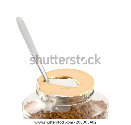 Metal teaspoon rests in a freshly opened jar of aromatic instant coffee granules - with copy space, isolated on a white background - stock photo