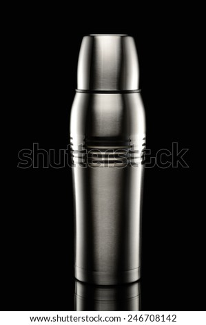 Metal thermos on black background - stock photo