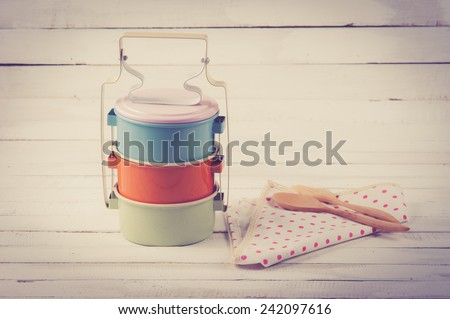 metal Tiffin,thai food carrier on wooden table background.vintage color toned image - stock photo