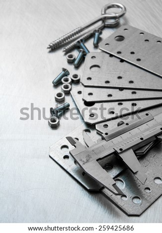 Metal tools. A calliper, metal blank and screws on the scratched metal background.