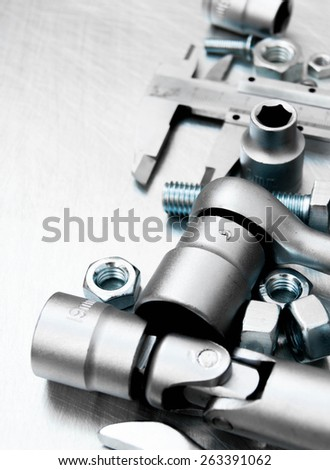 Metal tools. Wrench with a set of heads and other metal tools on the scratched metal background. - stock photo