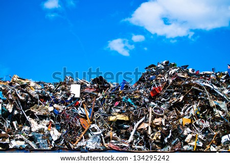 Metal waste on a recycling plant with sky and clouds
