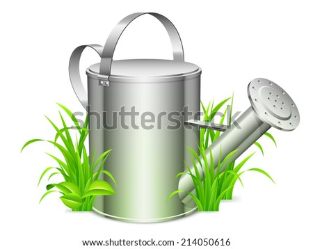 Metal watering can on green grass. - stock photo