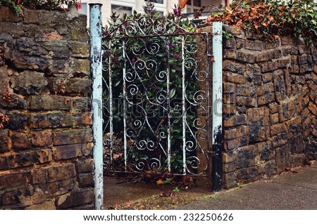 Metal wicket in a brick fence - stock photo