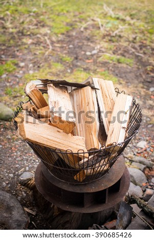 Metal wire basket filled with firewood outdoors - stock photo