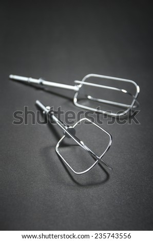 Metal wire whisk on dark background. Shallow depth of field. - stock photo