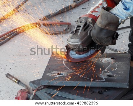 Metal worker in a factory grinding with sparks