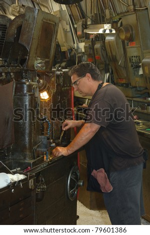 Metal worker in a factory operating a heavy machine - stock photo