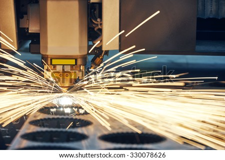 metal working. Laser cutting technology of flat sheet metal steel material processing with sparks. Authentic shooting in challenging conditions. - stock photo