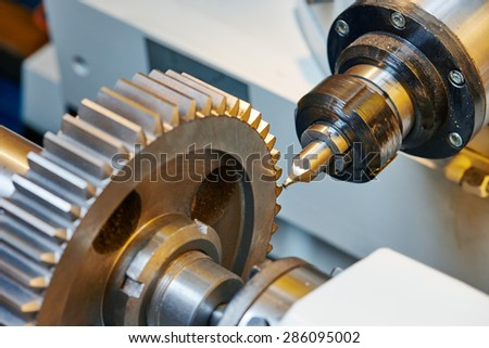 metal working. Process of tooth gear wheel finish machining by cutter tool at factory - stock photo
