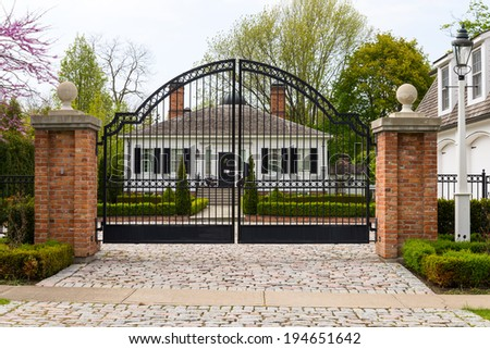 Metal wrought-iron gate and a house with landscaping  - stock photo
