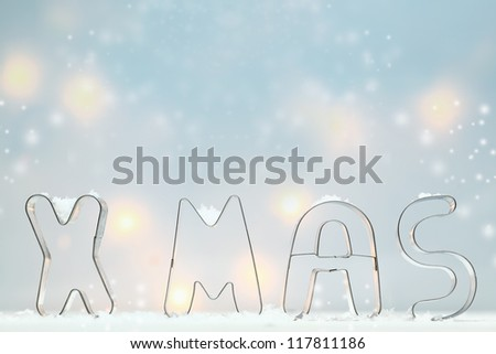 Metal Xmas cookie cutters standing in snow outlined against a soft blue atmospheric background with muted glowing lights and lots of copyspace for your Christmas greeting - stock photo
