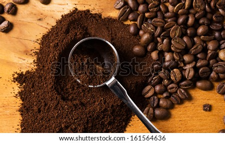 Metalic spoon and coffee over wooden surface - stock photo