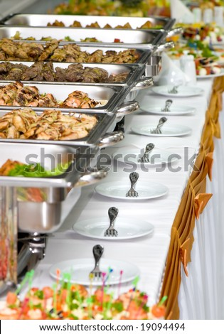 metallic banquet meal trays served on tables - stock photo