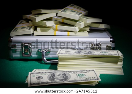 Metallic case with dollars on green table - stock photo