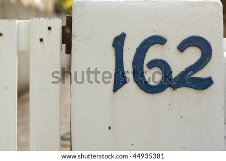 metallic house numbers on white picket fence - stock photo