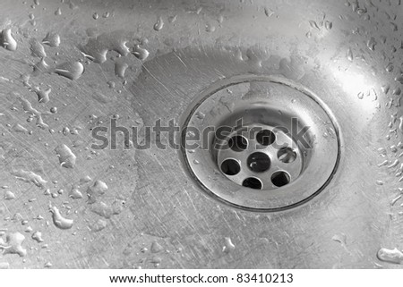 Metallic Kitchen sink with water drops shot from from low angle - stock photo