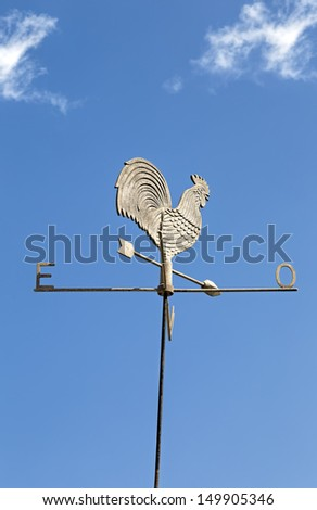 Metallic rooster wind cock vane brightly lit by the sun against clear blue sky - stock photo